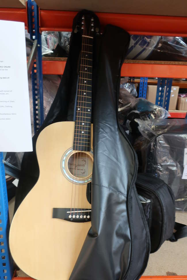 A pre-owned Martin Smith acoustic guitar in canvas case and a pre-owned Oscar Schmidt ukulele in canvas case.
