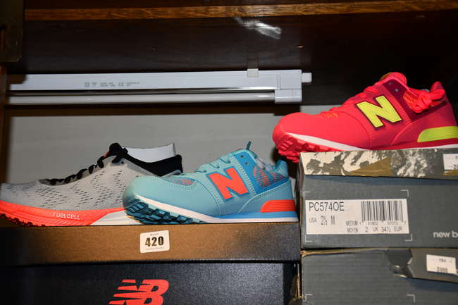 A pair of as new New Balance Fuelcell Impulse trainers (UK 5.5) together with two pairs of children's New Balance 574 trainers (Both EU 34.5).