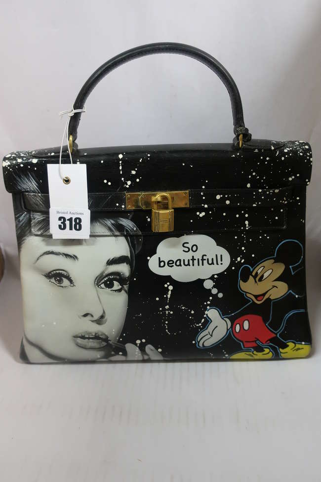 A vintage Hermes Kelly bag in black personalized with Audrey Hepburn and Mickey Mouse by streetart artist PatBo ( https://www.1stdibs.com/fashion/handbags-purses-bags/top-handle-bags/unique-handbag-hermes-kelly-32-black-box-calfskin-customized/id-v_6