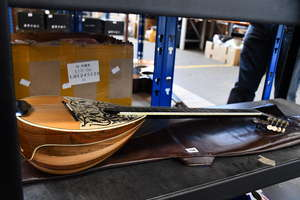 A round back eight string mandolin with mother of pearl  inlay with soft case.