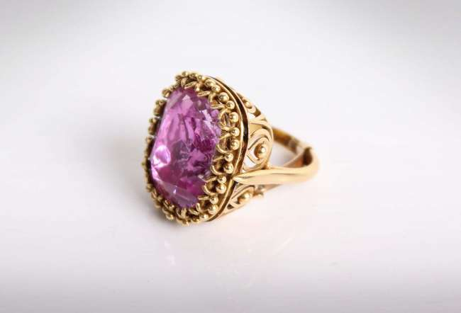 A 19th Century Pink Topaz Ring. Central cushion cut pink topaz approximately 16.40cts in a foiled mount and corded claw setting on a pierced and bead gallery with heavy 18ct gold shank. 14.1g Size K (fitted with sizing bar)