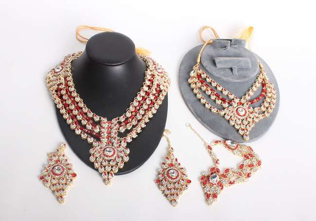 A collection of paste and yellow metal Indian wedding jewellery