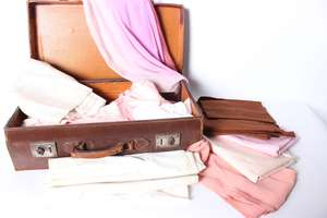 A collection of early 20th Century dressmaking fabric within a leather suitcase