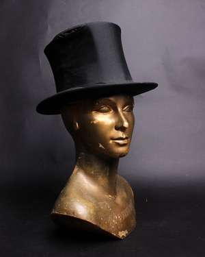 A 1920s blue straw hat decorated with grosgrain ribbon; a 1930s brown hat embellished with small silk and velvet flowers