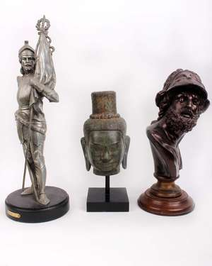 Three metal ware figures to include an Oriental Buddha head on stand