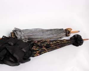 A 19th Century black silk machine embroidered parasol with a hand painted Sevres style handle