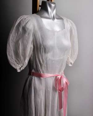 An early 20th Century full length voile dress embroidered with tiny pink flowers