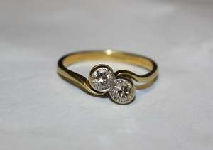 An 18ct gold 2 stone diamond crossover ring