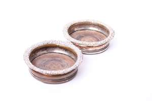 A pair of silver plated wine bottle coasters with raised floral rim and turned wooden bases.