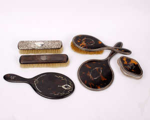 A tortoise shell and abalone shell inlaid hand held dressing table mirror together with matching brush and sterling silver topped brush.